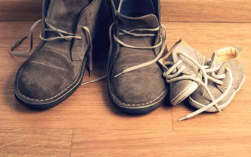 Father shoes beside daughters shoes